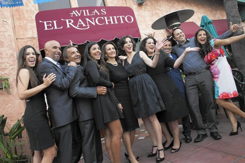 Second- and third-generation members of the Avila family pose for photos during a 50th anniversary celebration for Avila's El Ranchito restaurant Thursday in Costa Mesa.