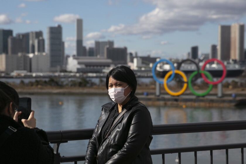 A tourist wearing a mask poses for a photo with the Olympic rings in Tokyo