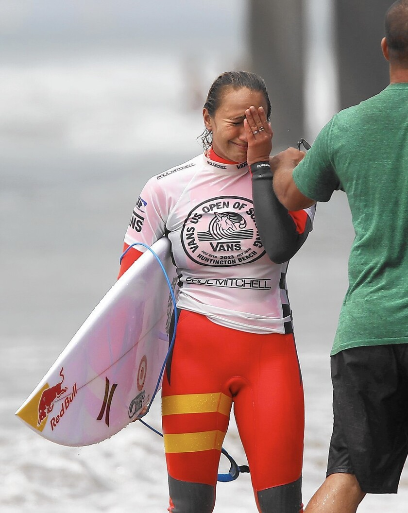 Hawaii's Carissa Moore is overcome by emotion after she learns she won the women's championship final of the 2013 Van's US Open of Surfing at the Huntington Beach Pier, Sunday.