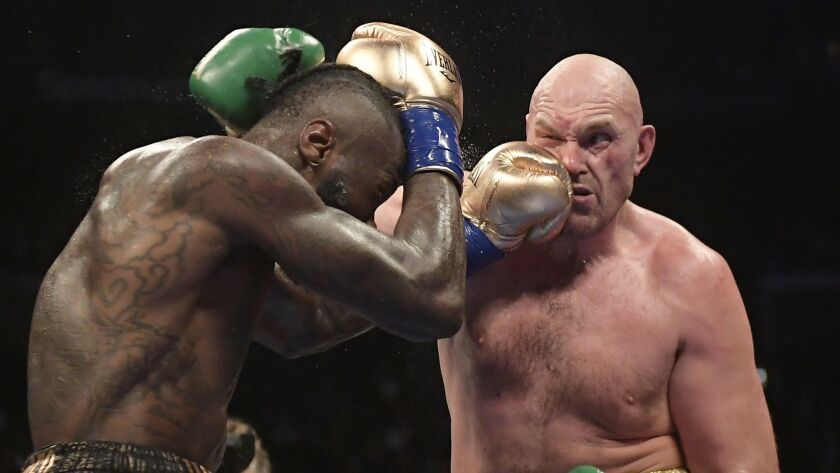 Deontay Wilder, left, connects with Tyson Fury during a WBC heavyweight championship boxing match.