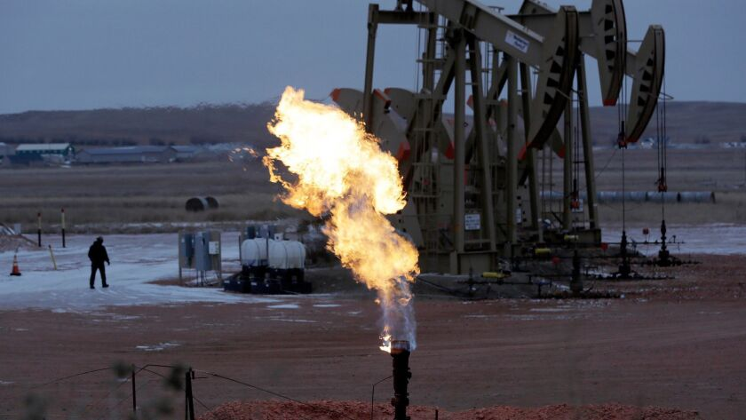 FILE - In this Oct. 22, 2015 file photo, workers tend to oil pump jacks behind a natural gas flare n