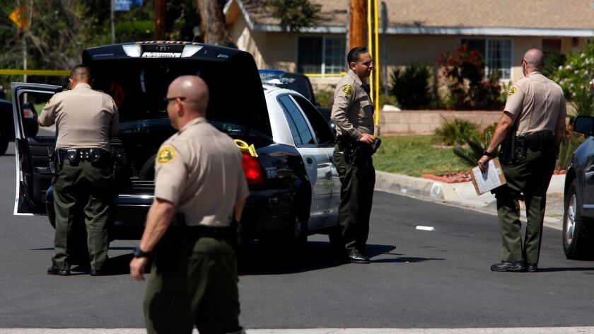 COVINA, CA - APRIL 9, 2017 -- Los Angeles County Sheriff deputies stand near a scene where an armed