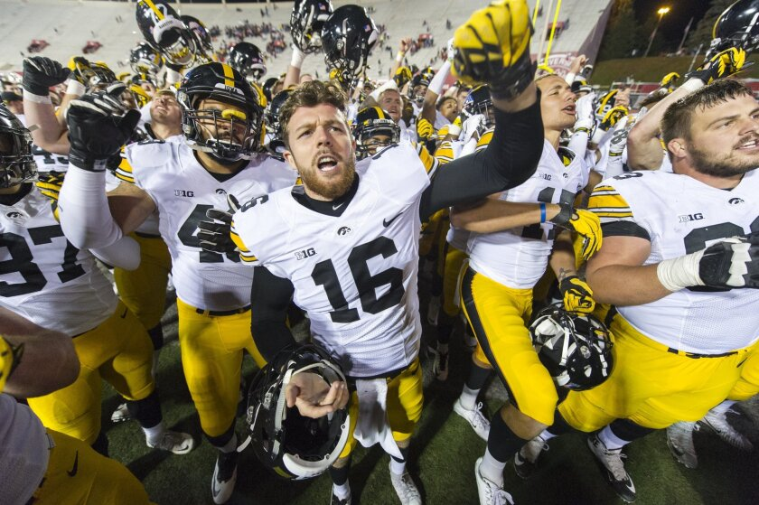 Iowa punter Dillon Kidd (16) and his teammates sing to their fans after an NCAA college football game against Indiana in Bloomington, Ind., Saturday, Nov. 7, 2015. Iowa won 35-27. (AP Photo/Doug McSchooler)