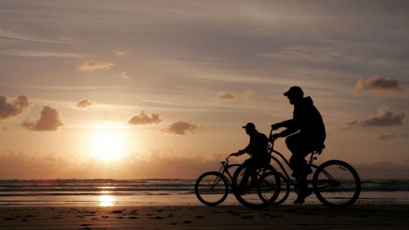 Two bicyclists ride along the water's edge at sunset at S. Cardiff State Beach along S. Coast Highway 101.