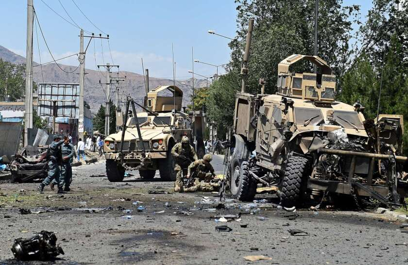 An NATO soldier helps a colleague who was injured in a suicide car bomb attack that targeted foreign military vehicles in the Afghan capital Kabul on June 30,2015.