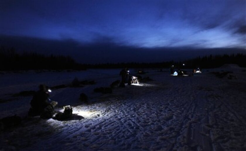 Headlamps provide light for mushers and veterinarians working with sled dogs in the village of Nikolai, Alaska during the Iditarod Trail Sled Dog Race, Tuesday, March 5, 2013. (AP Photo/Anchorage Daily News, Bill Roth)