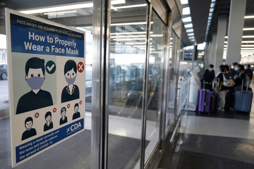 This July 2, 2021 photo shows a sign stating face coverings are required is displayed at O'Hare airport in Chicago. The nation's top aviation regulator is asking local officials to consider filing criminal charges more often against people who act up during airline flights, Thursday, Aug. 5. Federal Aviation Administration chief Stephen Dickson says airline crews often ask police to meet their plane when it lands because of unruly passengers. (AP Photo/Nam Y. Huh)