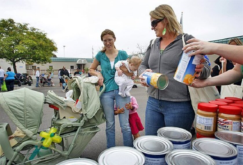 At the Murphy Canyon Armed Services YMCA, volunteer Courtney Bent  (right) helped Jennifer McCardle and her twin daughters at the first  monthly free-food distribution service yesterday.  (K.C. Alfred / Union-Tribune)