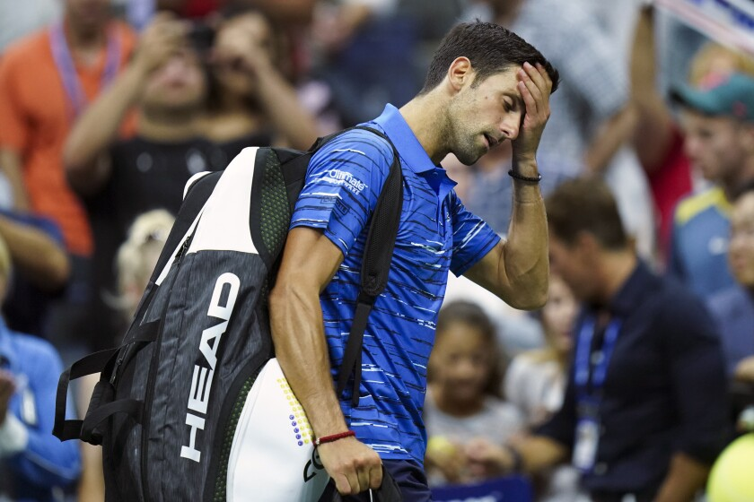 Novak Djokovic walks off the court after retiring during his match against Stan Wawrinka on Sunday at the U.S. Open.