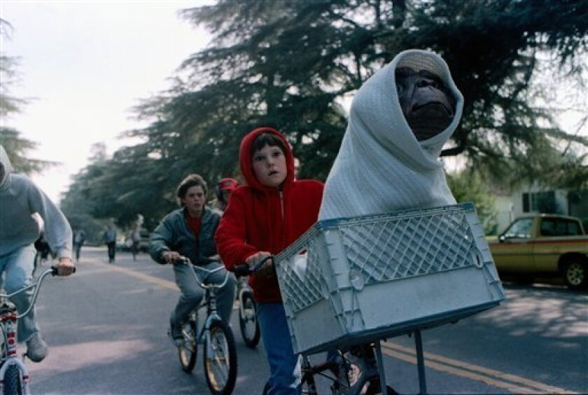 """This undated publicity film image released by Universal Pictures shows Henry Thomas as Elliott and E.T. in a basket on a bicycle in a scene from director Steven Spielberg's """"E.T.: The Extra-Terrestrial."""" In honor of the 30th anniversary of """"E.T.,"""" a digitally remastered feature film returns to theaters Oct. 3, 2012, along with a Blu-ray Anniversary Edition available Oct. 9. (AP Photo/Universal Pictures)"""