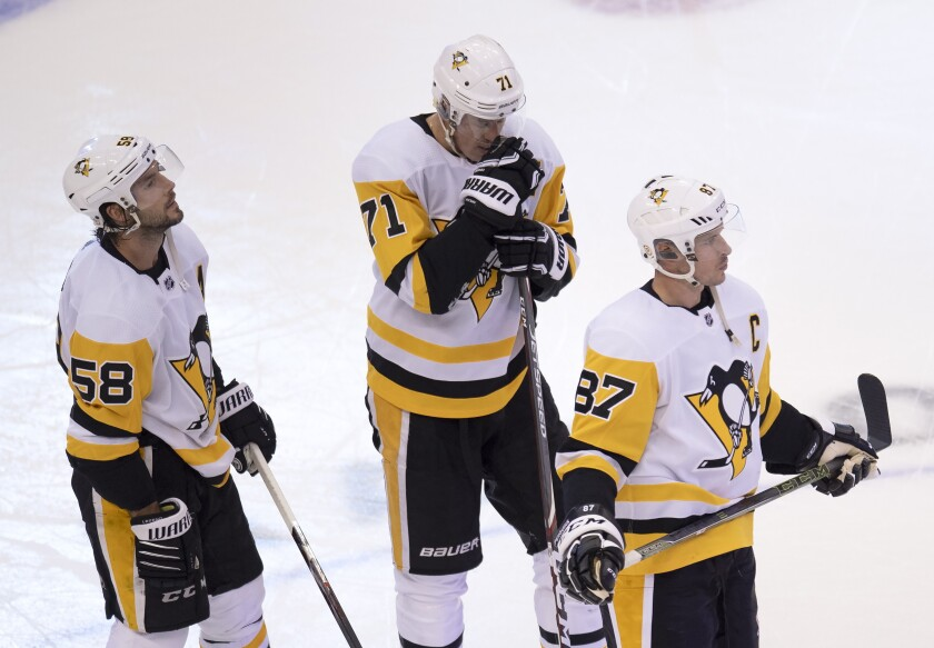 Pittsburgh Penguins center Sidney Crosby (87), center Evgeni Malkin (71) and defenseman Kris Letang (58) react after losing to the Montreal Canadiens in an NHL hockey playoff game Friday, Aug. 7, 2020, in Toronto. (Frank Gunn/The Canadian Press via AP)