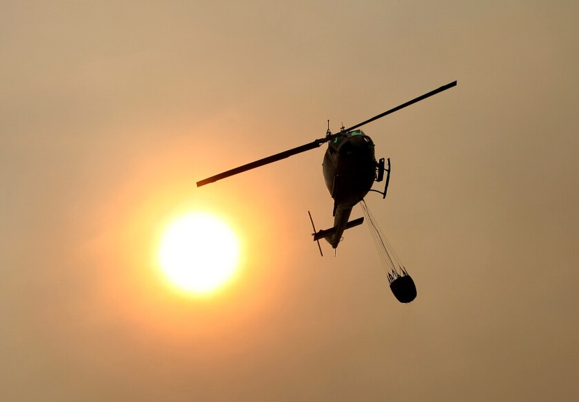 A California Department of Forestry and Fire Protection helicopter flies over Pfeiffer Ridge as a wildfire raged in the Big Sur area.