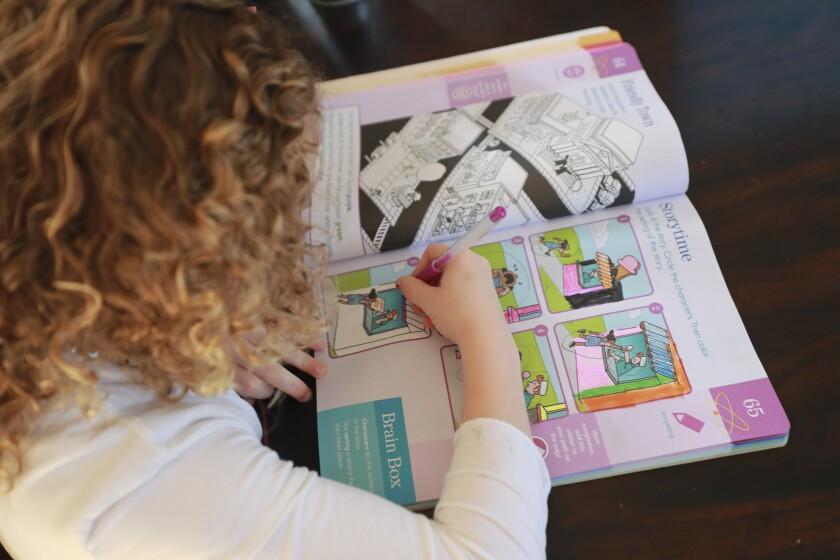 Nina Jensen, 5, works on an activity book.