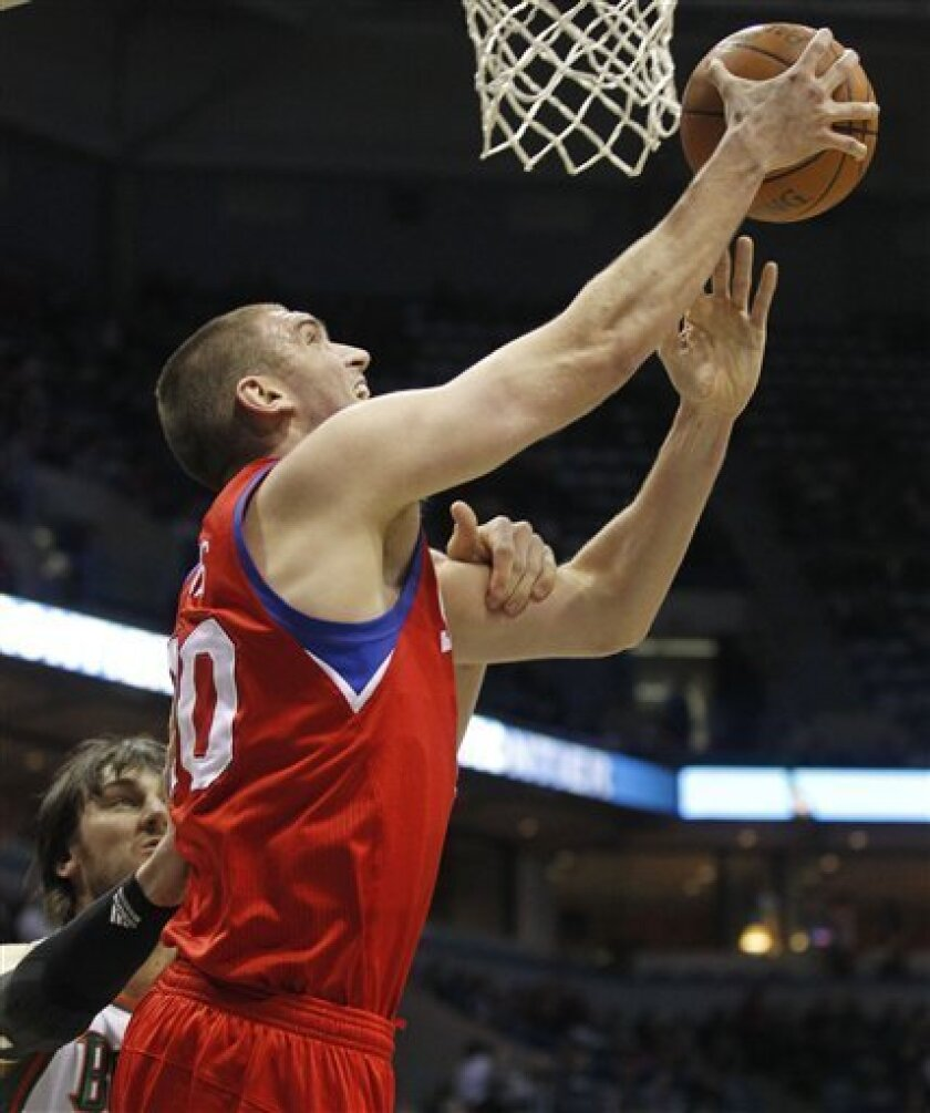 Milwaukee Bucks' Andrew Bogut, left, fouls Philadelphia 76ers' Spencer Hawes in the first half of an NBA basketball game Saturday, April, 2, 2011, in Milwaukee. (AP Photo/Jeffrey Phelps)