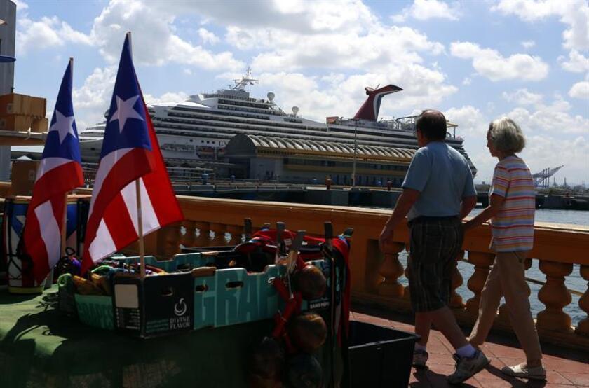 Fotografía donde aparecen dos turistas paseando frente a un crucero en el Puerto de San Juan que se está recuperando lentamente después del paso de los huracanes Irma y María. EFE/Archivo