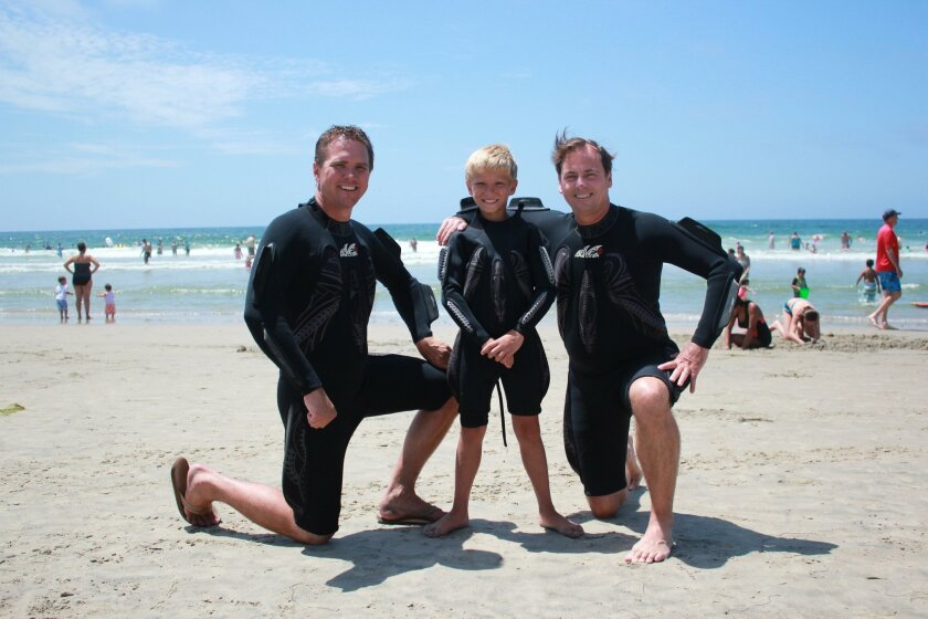 Wearing the Wave Wrecker are company vice-president Mike Van Nostram and his son Bradley, age 9, with the wetsuit's designer, Nick Gadler