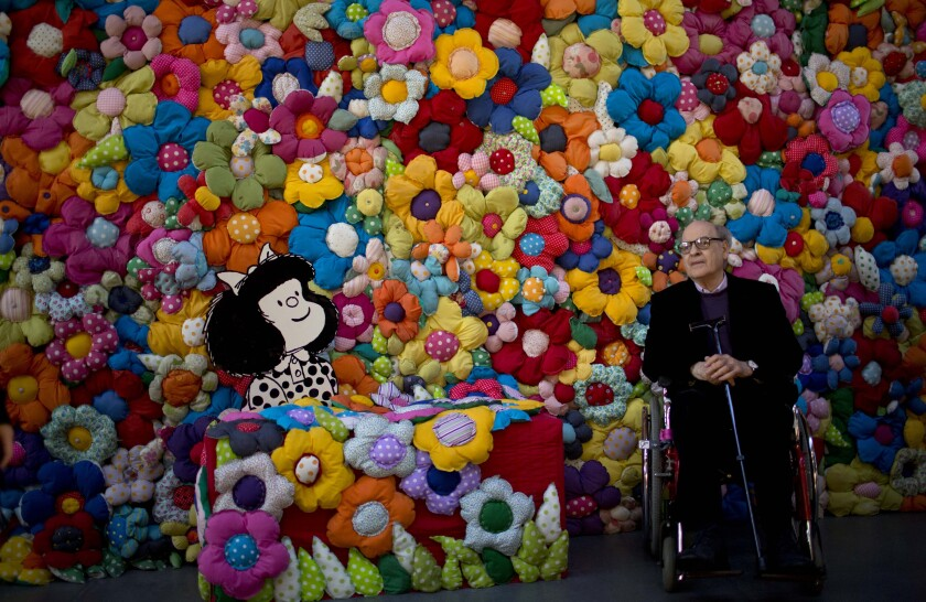 "Argentine cartoonist Joaquin Salvador Lavado, better known as ""Quino,"" poses next to his character Mafalda in 2014."