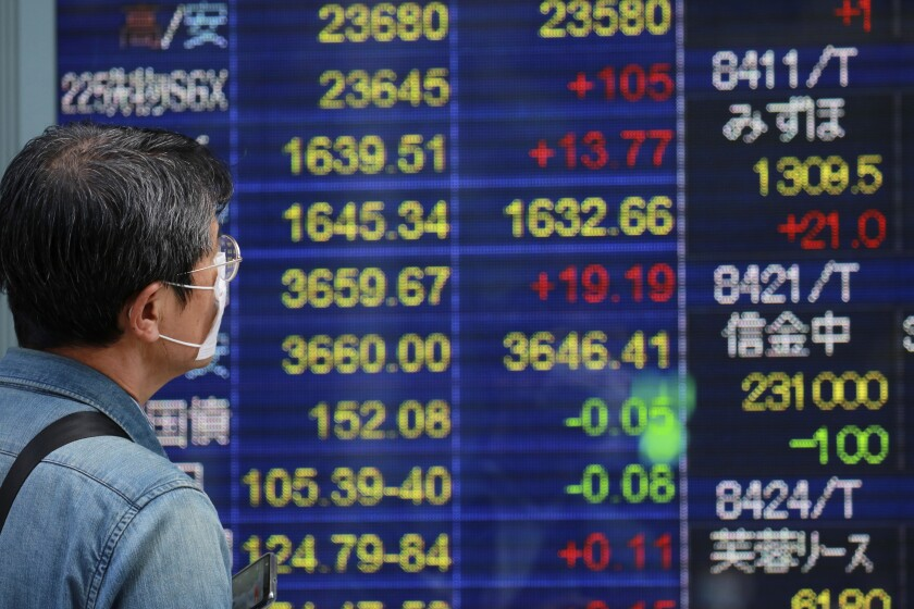A man looks at an electronic stock board of a securities firm in Tokyo, Wednesday, Oct. 21, 2020. Asian shares mostly rose Wednesday, cheered by the gains on Wall Street as investors welcomed a batch of solid earnings reports from U.S. companies.(AP Photo/Koji Sasahara)