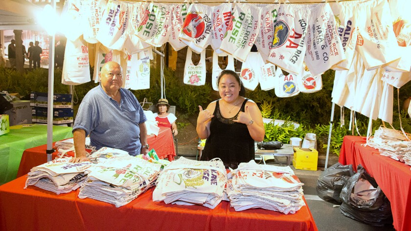 During the block party that takes over Kalakaua Avenue in Honolulu, a vendor sells pairs of shorts made from rice bags.