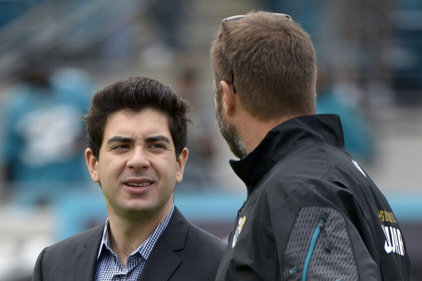 FILE - In this Dec. 15, 2013, file photo, Jacksonville Jaguars senior vice president Tony Khan, left, talks with an unidentified person prior to an NFL football game against the Buffalo Bills in Jacksonville, Fla. Tony Khan has his hands full as co-owner of the Jacksonville Jaguars and with Fulham F.C. of the EFL Championship. He decided to launch his own wrestling company and now All Elite Wrestling is not only nipping at WWE's heels as best in the business, it's set to take over New York on Wednesday night with its Grand Slam event from Arthur Ashe Stadium. (AP Photo/Phelan M. Ebenhack, File)