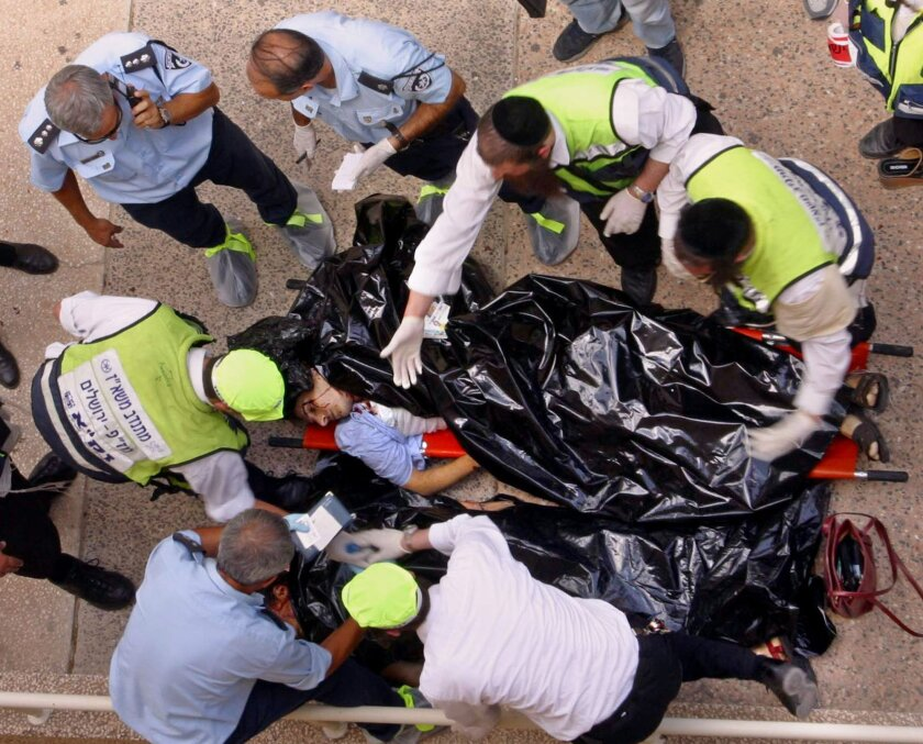 FILE - In this July 31, 2002 file photo. police and volunteers examine the body of one of the victims of an explosion at Hebrew University of Jerusalem. Palestinian officials are nervously watching a landmark terrorism trial in the U.S brought by victims of Palestinian suicide bombings and shootings aimed at civilians, fearing a negative verdict could hurt their international image at a time when they are preparing to press war crimes charges against Israel. (AP Photo/John McConnico, File)