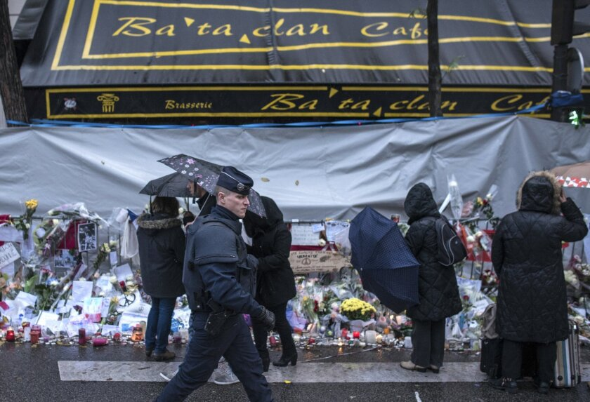 FILE - In this Nov. 25, 2015 file photo, a policeman walks as people pay respects to victims of the Paris attacks in front of the Bataclan concert hall, in Paris. The owners of the Paris concert hall where 89 people were massacred by Islamic extremists say Wednesday Feb.10, 2016 they are aiming to