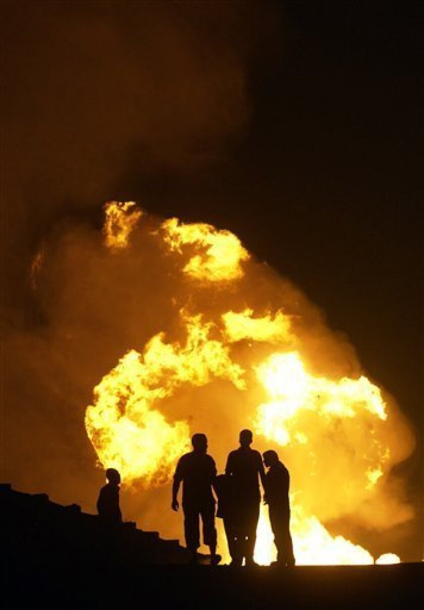 Egyptian Bedouins stand next to leaping flames after masked gunmen blew up a terminal of the Egyptian natural gas pipeline to Israel and Jordan in El Arish, in the northern part of Egypt's Sinai Peninsula, early, Tuesday, July 12 2011, Security officials say. (AP Photo)