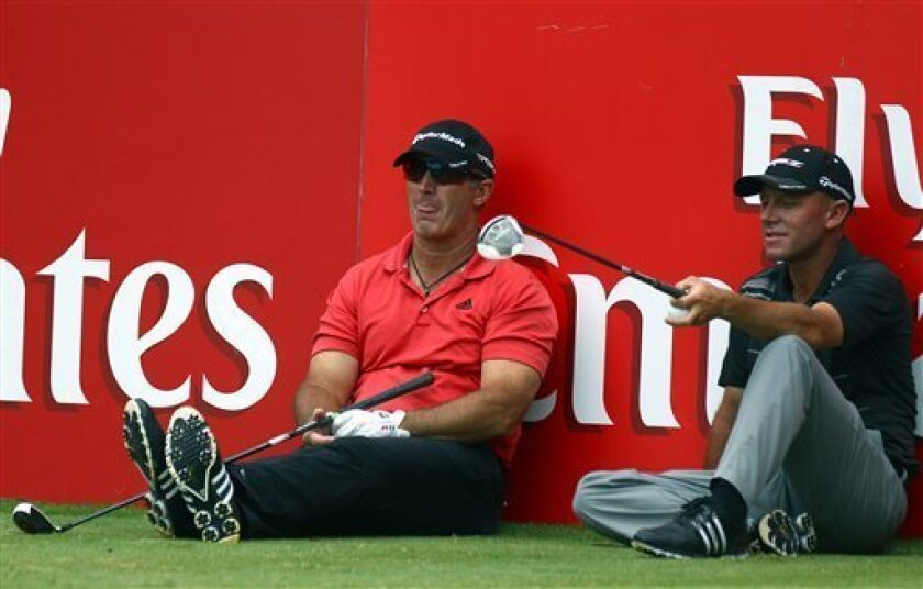 Australia's Peter Lonard, left, and Nathan Green, relax on the 16th tee while waiting for their turn to hit off during the final round of the Australian Open golf tournament at the Lakes Golf Course in Sydney, Sunday, Dec. 9, 2012. (AP Photo/Rick Rycroft)