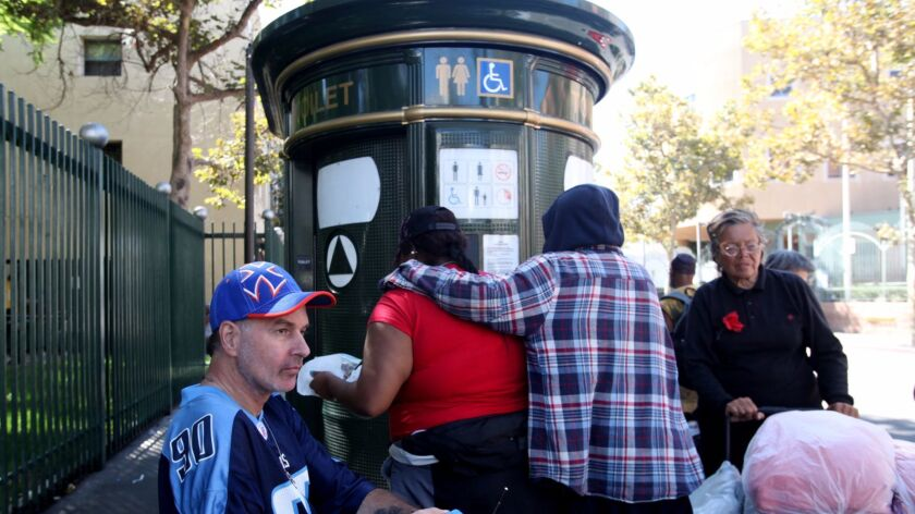 LOS ANGELES, CA - JULY 30, 2013: Ricardo Albrecht, left, waits outside one of the public toilets at