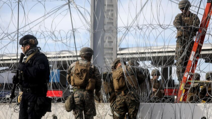 A U.S. Customs and Border Protection agent, left, stands watch on Thanksgiving Day as troops set up concertina wire at the San Ysidro border crossing into Tijuana, Mexico.