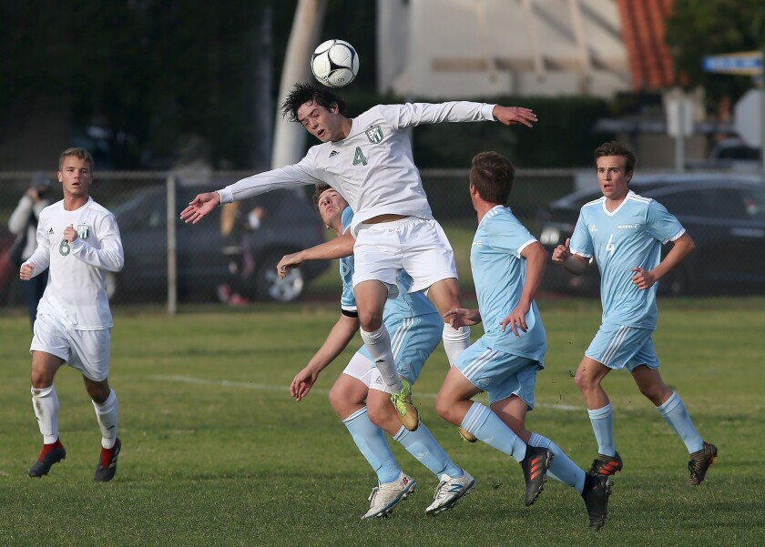Edison's Chase Bullock (4) heads the ball upfield surrounded by a host of Corona del Mar defenders i