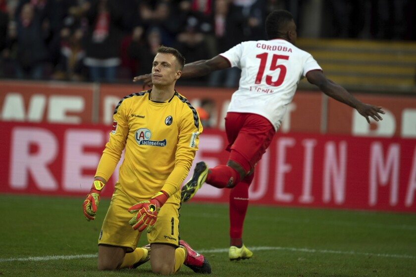 Cologne's Jhon Cordoba celebrates scoring his side's second goal of the game as Freiburg's goalkeeper Alexander Schwolow, left, looks dejected during their German Bundesliga soccer match between FC Cologne and SC Freiburg at the RheinEnergie Stadium in Cologne, Germany, Sunday, Feb. 2, 2020. (Federico Gambarini/dpa via AP)