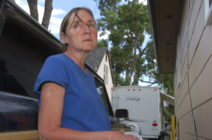 In this Wednesday, July 22, 2015 photo, Regina Culver stands outside the window of her Billings, Mont., home through which her 17-year-old son shot and killed a friend who was knocking on her son's window late at night. Culver says she doesn't think criminal charges are warranted in a case that prosecutors plan to put before a special coroner's jury. (AP Photo/Matthew Brown)