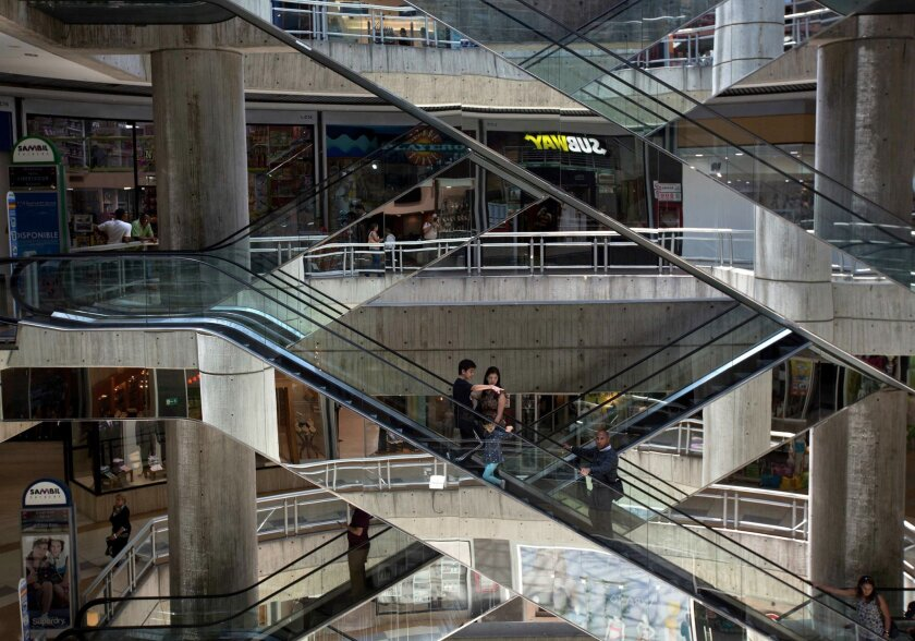FILE - In this April 10, 2014, file photo, people ride the nearly empty escalators inside Sambil mall, in Caracas, Venezuela. Shopping malls across Venezuela are preparing to dramatically reduce their hours to comply with electricity rationing. The South American country's socialist government orde