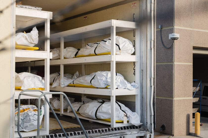 Bodies wrapped in plastic are stacked inside a mobile morgue set up by the medical examiner's office in El Paso on Friday.