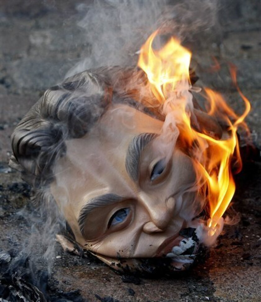 A mask of former British Prime Minister Tony Blair is burnt by a demonstrator, outside the Iraq Inquiry in London, Monday, Nov. 30, 2009, where David Manning, a key adviser to former British Prime Minister Tony Blair  was testifying about decisions made before the Iraq war. The inquiry is the most