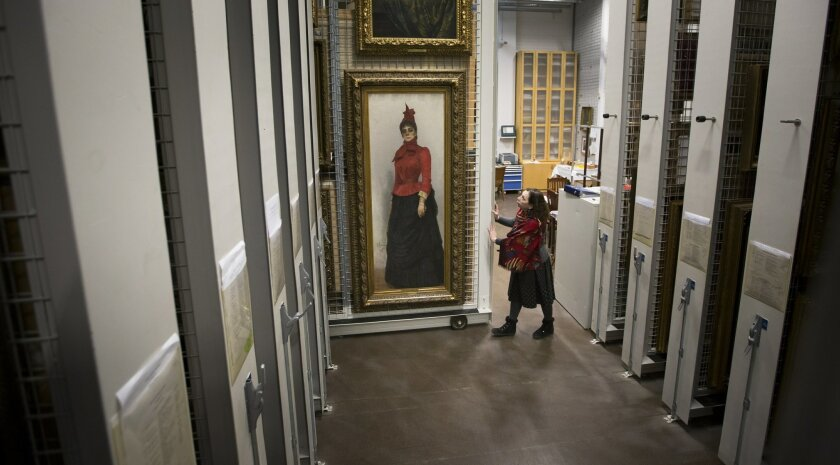 In this photo taken on Thursday, Feb. 11, 2016, researcher Svetlana Kapyrina looks at Ilya Repin's painting of Baroness Varvara Ikskul von Hildenbandt at Moscow's Tretyakov Gallery, Russia, as preparations are made for 26 works of art to be shipped from Moscow to Britain's National Portrait Gallery for an exhibition. Cultural exchange between Russia and the West is alive and well, even in difficult political and economic times, says the director of Moscow's Tretyakov Gallery, as her staff pack up some of Russia's finest paintings, to be sent to London for a landmark exhibition. The 26 portraits being sent to the National Portrait Gallery for a March17-June 26 exhibition are part of an exchange that include major British works loaned to Russia. Despite chill relations with the West and an economic crisis in Russia, the shows will go ahead because the two museums are determined to cooperate, Tretyakov director Zelfira Tregulova said. (AP Photo/Alexander Zemlianichenko)