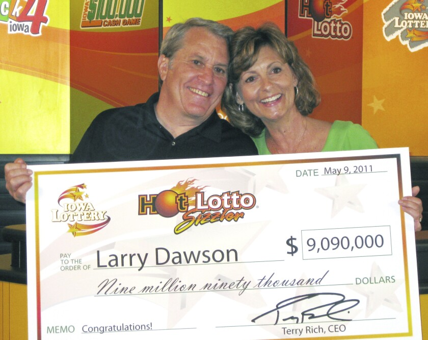 This May 9, 2011 photo provided by the Iowa Lottery shows Larry Dawson and his wife, Kathy, claiming their $9.09 million Hot Lotto jackpot in Des Moines. A national lottery group rocked by an insider's jackpot-rigging conspiracy has settled a lawsuit brought by the Iowa grandfather who said the $9 million prize he won in 2011 should have been nearly three times as big. The Multi-State Lottery Association and Dawson informed a judge of the settlement this month, cancelling a trial that had been scheduled to begin next week in Des Moines, Iowa. (Iowa Lottery via AP)
