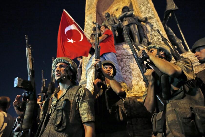 Soldados turcos aseguran una zona mientras partidarios del presidente de Turquía, Recep Tayyip Erdogan, protestan en la plaza Taksim de Estambul en la madrugada del sábado 16 de julio de 2016. (AP Foto/Emrah Gurel)