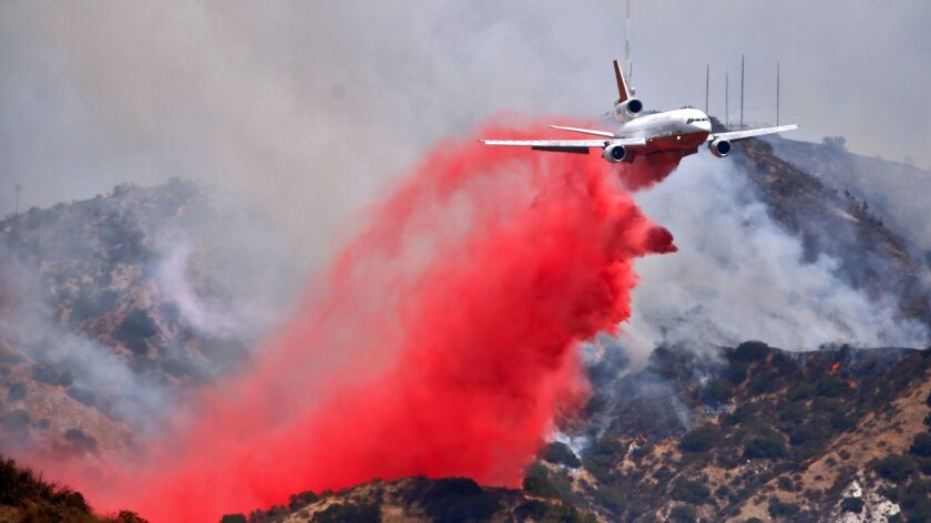 A DC-10 drops fire retardant on the Verdugo Hills above Burbank as multi-agency crews battle the La