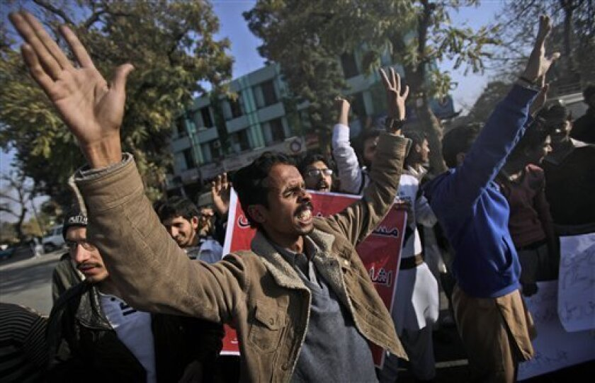 Pakistanis chant slogans supporting Mumtaz Qadri, alleged killer of Punjab governor Salman Taseer, during a rally in Islamabad, Pakistan, Monday, Jan. 10, 2011. Salman Taseer was killed on Tuesday by his bodyguard commando reportedly enraged by his opposition to laws decreeing death for insulting Islam. (AP Photo/Muhammed Muheisen)