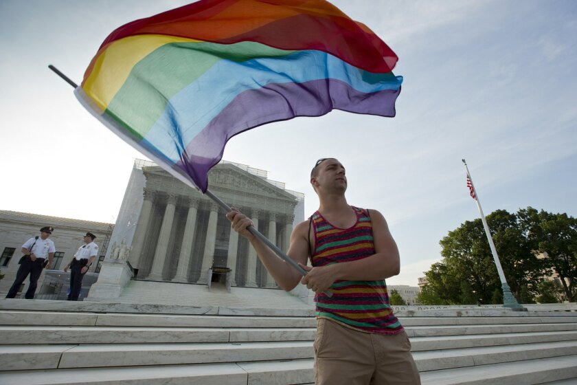 FILE- In this June 26, 2013, file photo, gay rights advocate Vin Testa waves a rainbow flag in front of the Supreme Court in Washington. (AP Photo/J. Scott Applewhite, File)