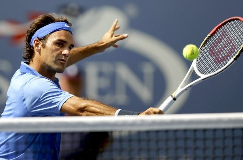 Roger Federer reaches for a volley during a second-round match against Carlos Berlocq on Thursday at the U.S. Open.