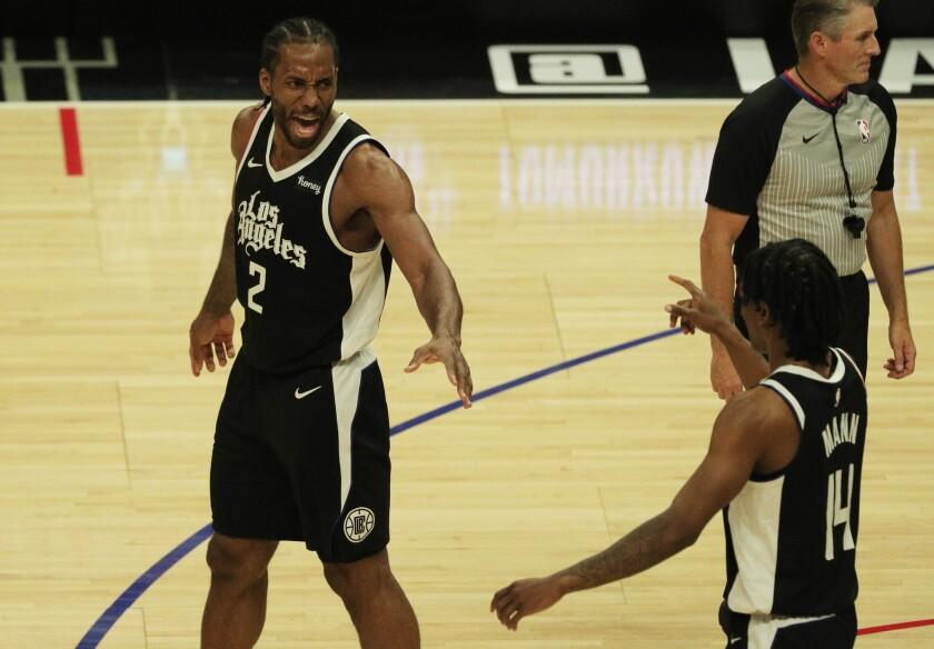 Clippers forward Kawhi Leonard, left, and guard Terance Mann celebrate during a 126-111 win over the Dallas Mavericks.