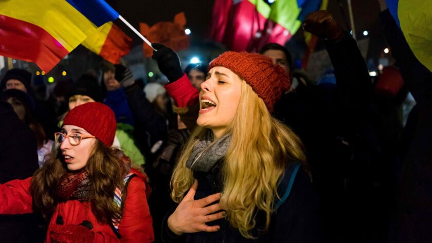 A young woman sings during a protest against the government in Bucharest, Romania, on Sunday.