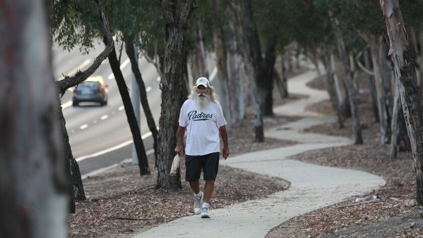 John Justice walks along a paved path surrounded by trees, some of them eucalyptus trees, on Twin Peaks Road in Poway on Tuesday.
