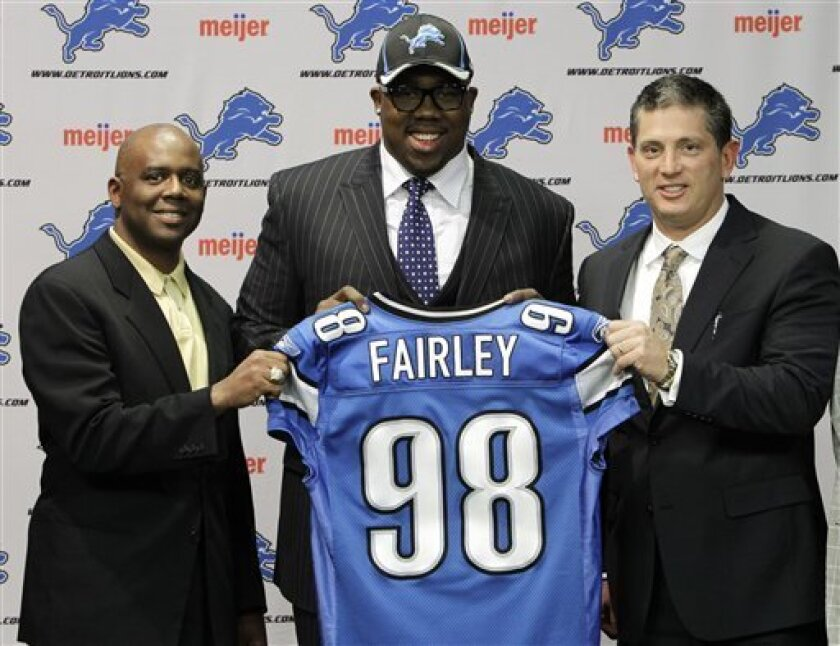 Detroit Lions general manager Martin Mayhew, from left, first-round draft pick Nick Fairley, and head coach Jim Schwartz pose at the team's headquarters in Allen Park, Mich., Friday, April 29, 2011. Fairley was selected 13th overall in the 2011 NFL draft. (AP Photo/Paul Sancya)