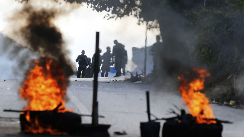 Bolivarian National Police stand behind a burning roadblock set up by anti-government protesters who