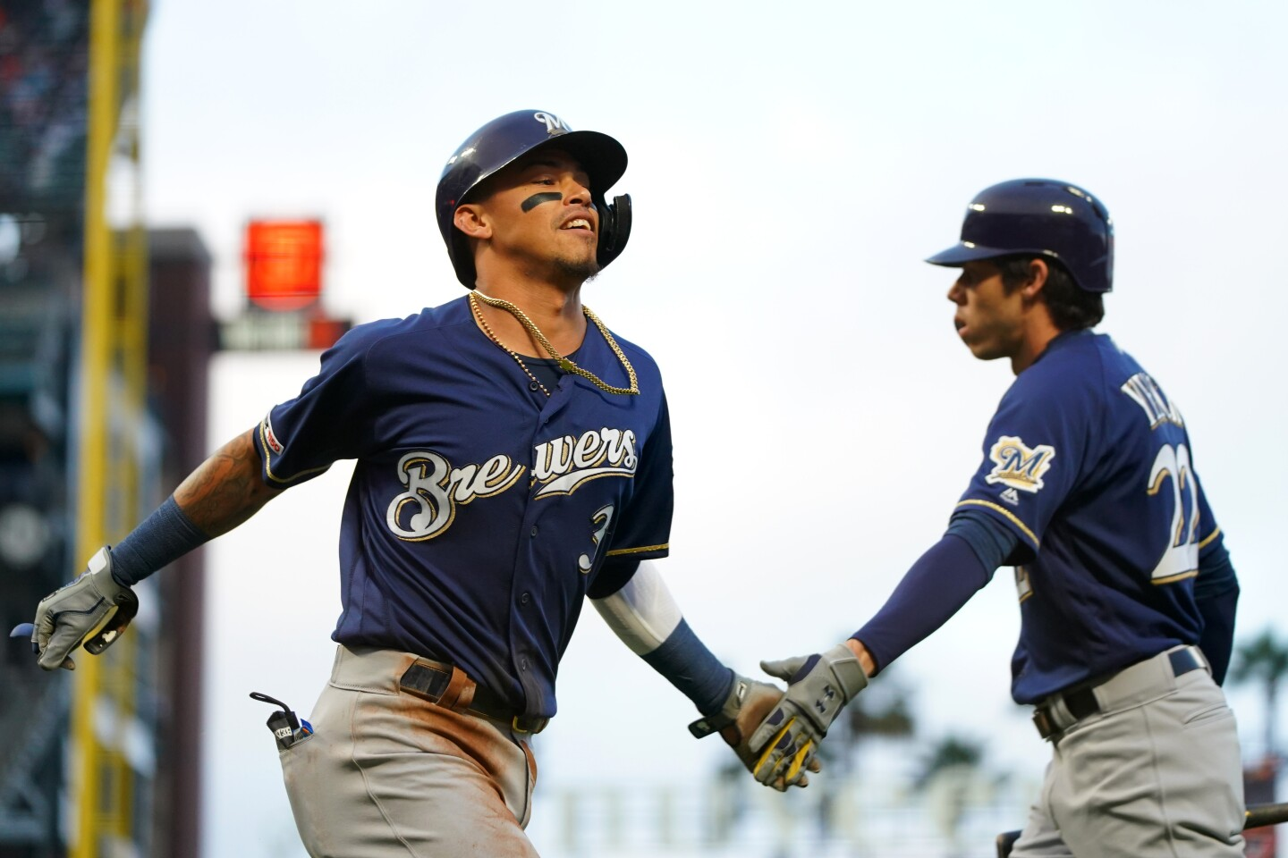 SAN FRANCISCO, CALIFORNIA - JUNE 14: Orlando Arcia #3 of the Milwaukee Brewers celebrates with Christian Yelich #22 after scoring on a past ball during the third inning against the San Francisco Giants at Oracle Park on June 14, 2019 in San Francisco, California. (Photo by Daniel Shirey/Getty Images) ** OUTS - ELSENT, FPG, CM - OUTS * NM, PH, VA if sourced by CT, LA or MoD **