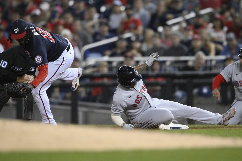Boston Red Sox' Rafael Devers, right, makes it back safely to first against Washington Nationals first baseman Josh Bell (19) on a fly out by Hunter Renfroe during the fourth inning of a baseball game Friday, Oct. 1, 2021, in Washington. (AP Photo/Nick Wass)